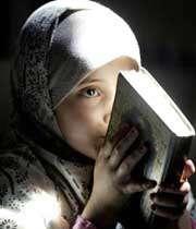 دختر بچه ای در حال بوسیدن قرآن