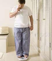 مردی در حال اندازه گیری وزن خود بر روی وزنه