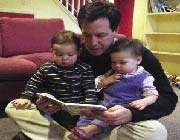 father reading books to his children