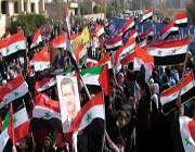 syrian demonstrators waving syrian and palestinian flags during a pro-government rally in the eastern city of deir zor, january 20, 2012.